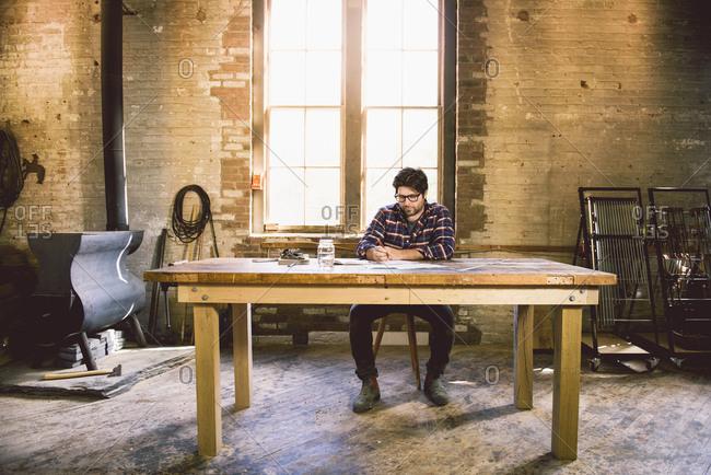 Carpenter at table writing
