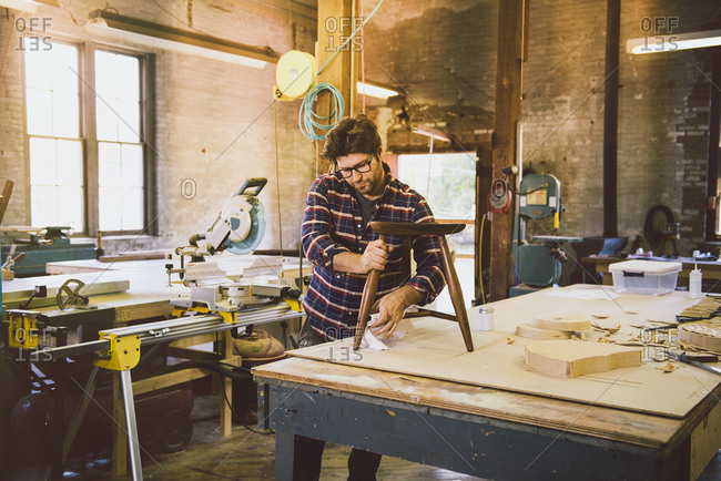 Man in woodshop wiping stool
