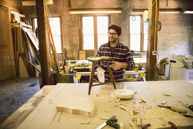 Carpenter wiping down stool
