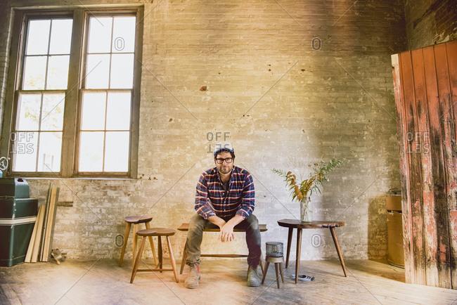 Carpenter sitting on table in workshop