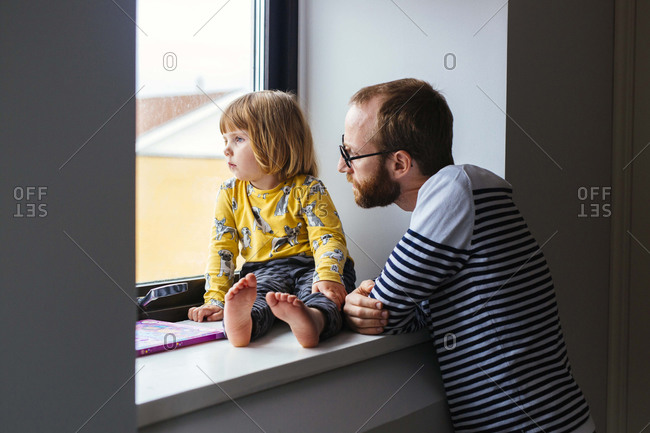 Dad and girl in window with book