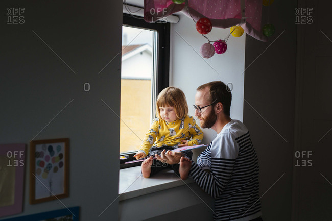 Girl reading book in window with dad