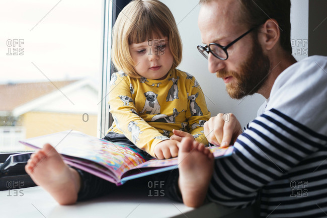 Dad reading with girl in window