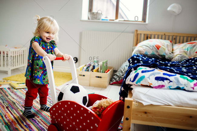 Girl pushing toy cart in bedroom