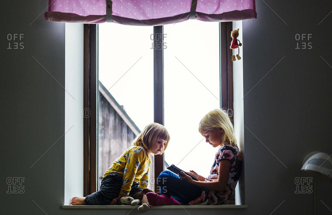 Girls in windowsill with tablet