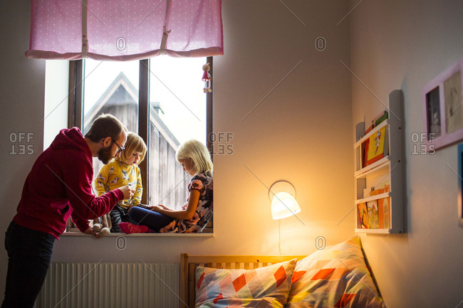 Dad with girls reading in window
