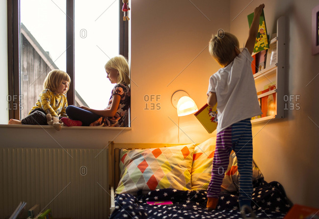 Three kids in bedroom reading