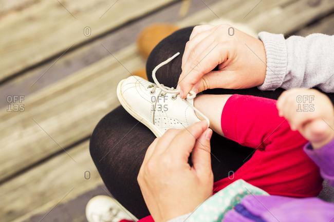 Hands helping tie child's shoe