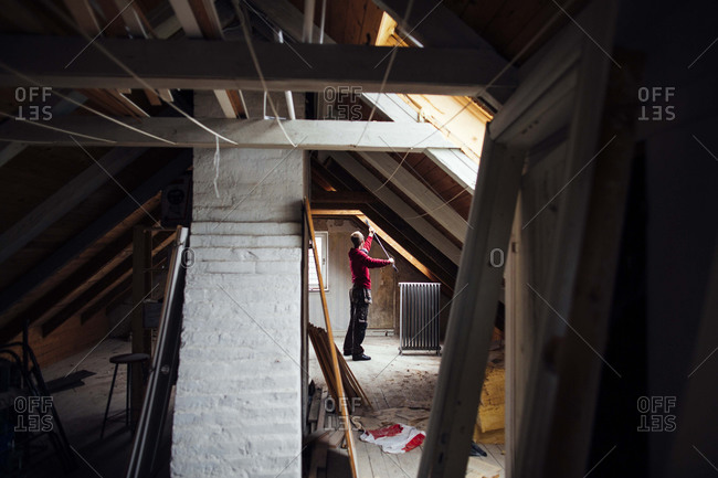 Man pulling out nails in attic