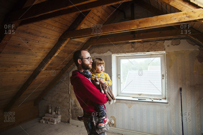 Man holding girl in attic rehab