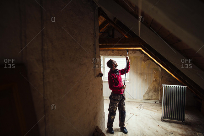 Man removing nails in attic