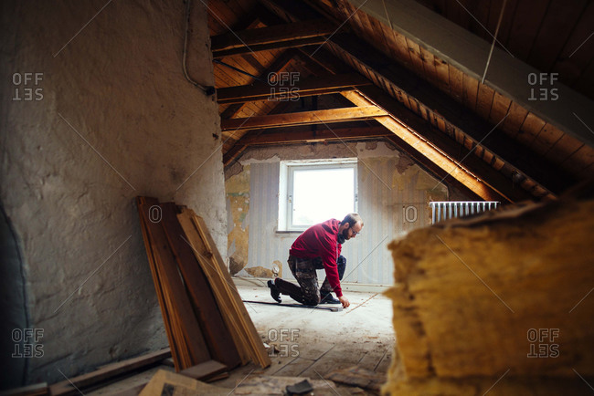 Man pulling up nails in attic
