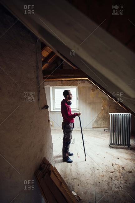 Man with crowbar standing in attic
