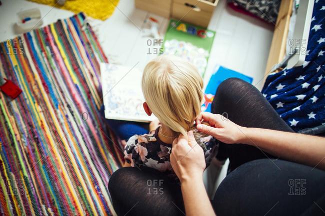 Pregnant woman braiding girl's hair