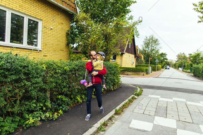 Man carrying girl with scooter