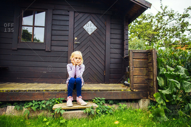 Girl with head in hands on cabin porch