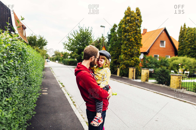 Man comforting crying girl on sidewalk