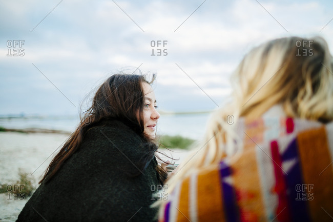 Women wrapped in blankets on beach