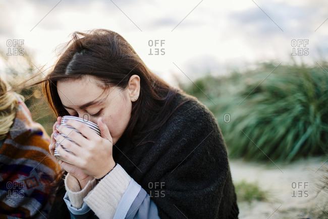 Woman drinking from mug on beach