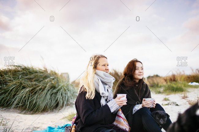 Women with mugs and dog on beach