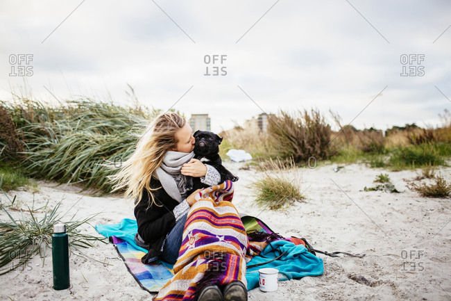 Woman kissing her dog on beach