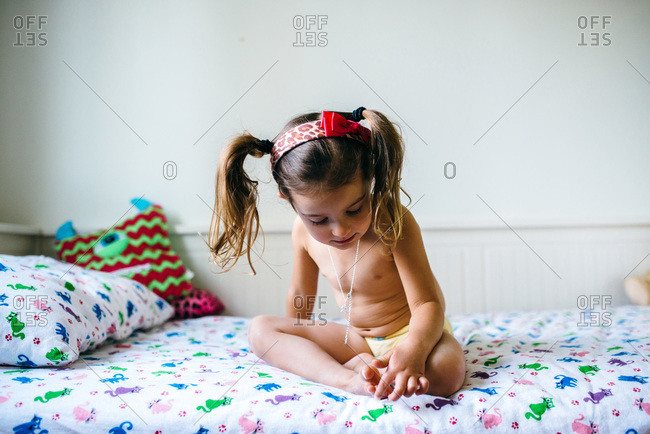 Little girl sitting on her bed