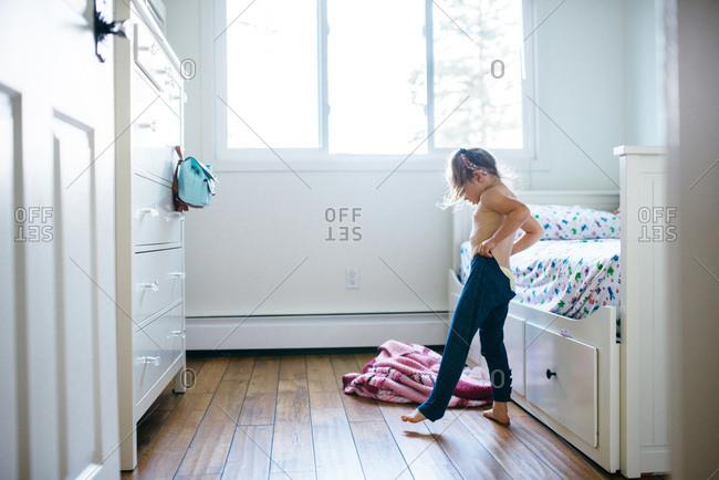 Little girl getting dressed in her bedroom