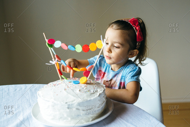 Little girl about to stick her finger into the icing on her birthday cake