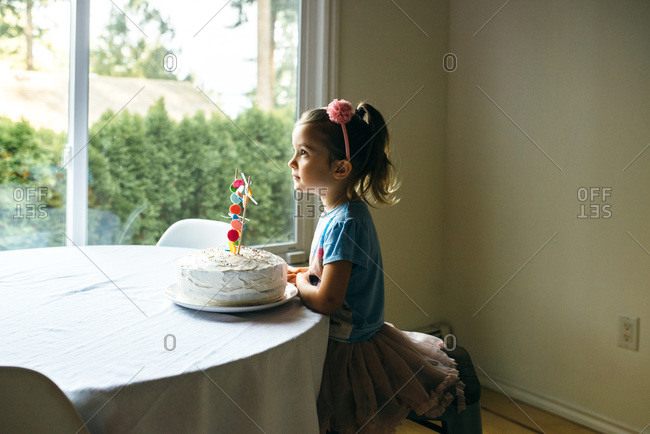 Little girl waiting patiently with her birthday cake