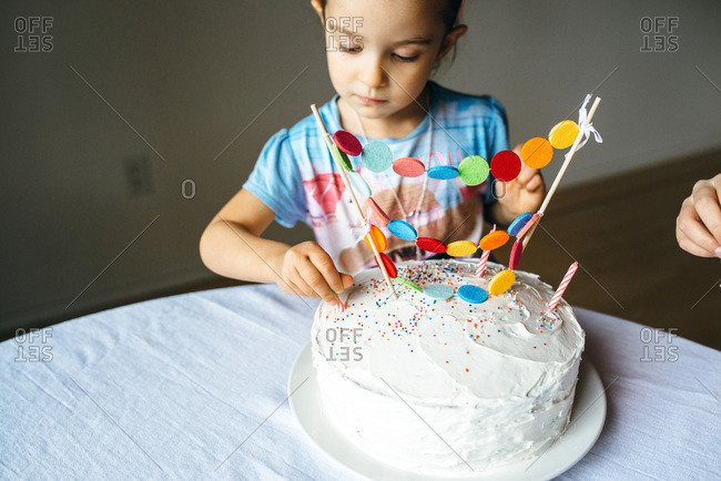Girl placing a candle on a birthday cake