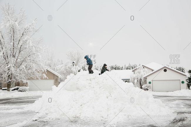 Boys playing on a huge mound of snow