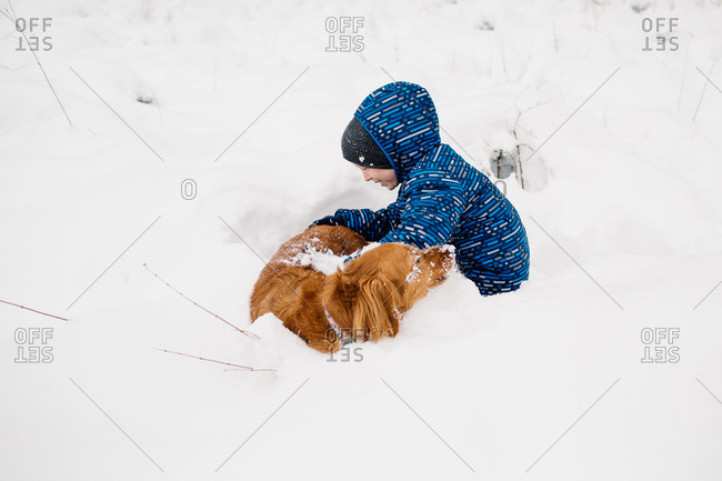 Boy playing with his dog in the snow