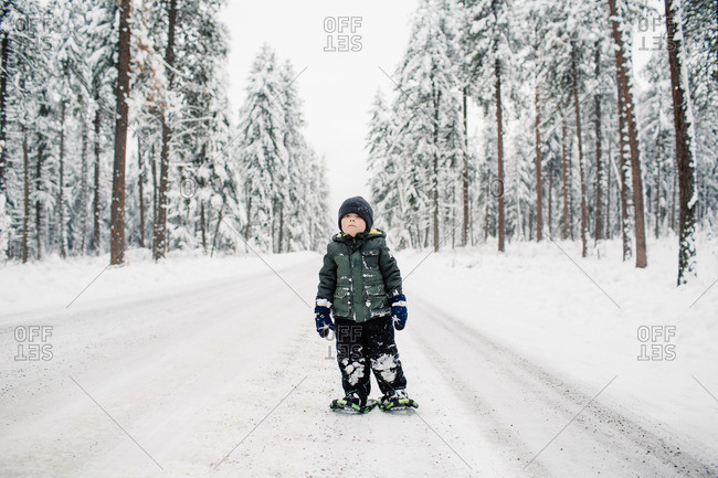 Boy wearing snowshoes on a wintry wooded road