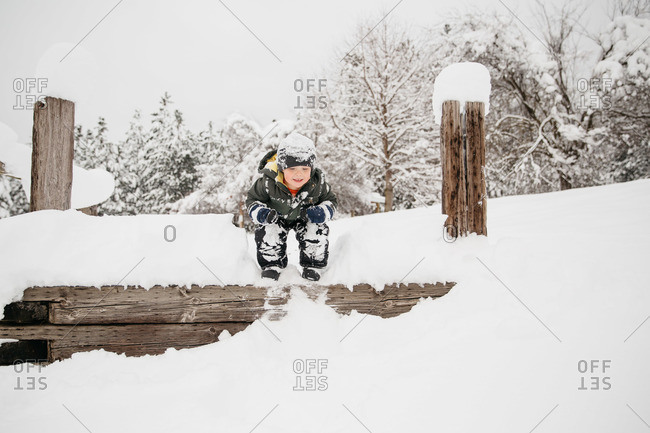 Boy jumping off a wooden ledge into the snow