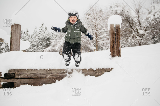 Boy leaping off a wooden ledge into the snow