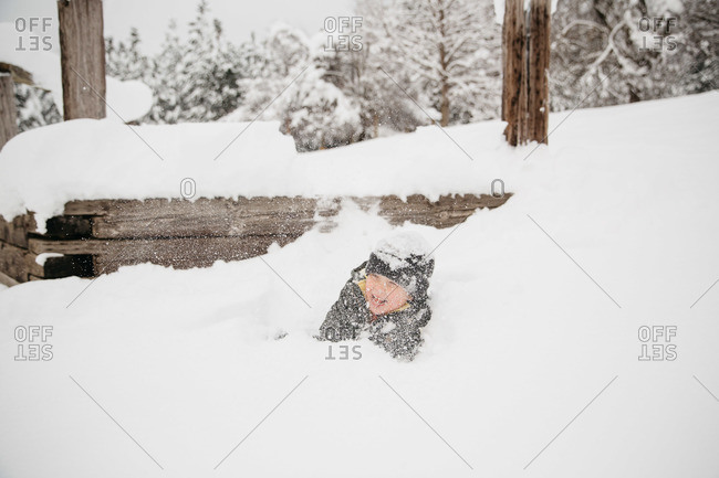 Boy landing in snow after jumping off a ledge