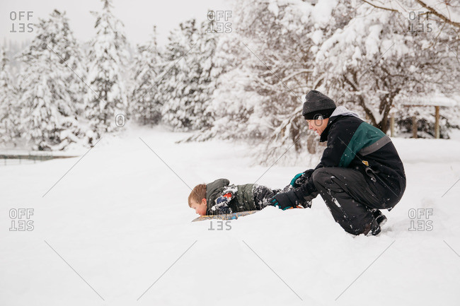 Father pushing his son on a sled