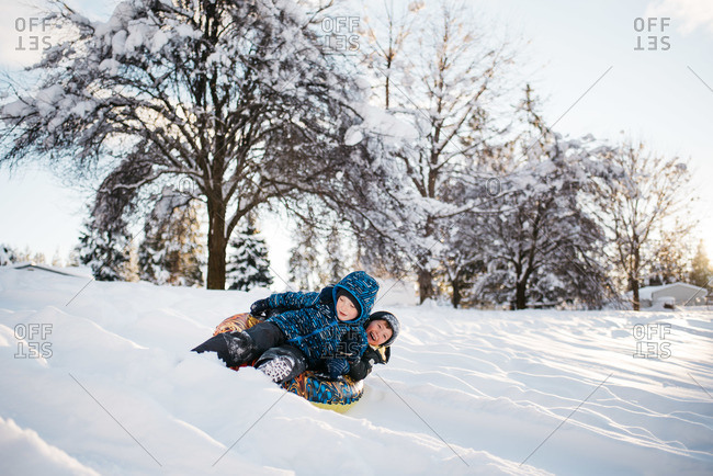 Boys sledding together in the snow