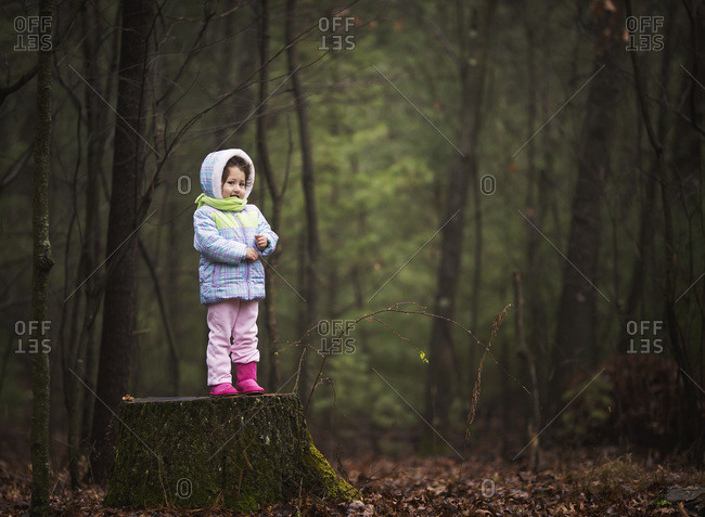 Girl standing in a forest in damp, chilly weather