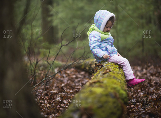 Girl sitting on a log in a forest in winter