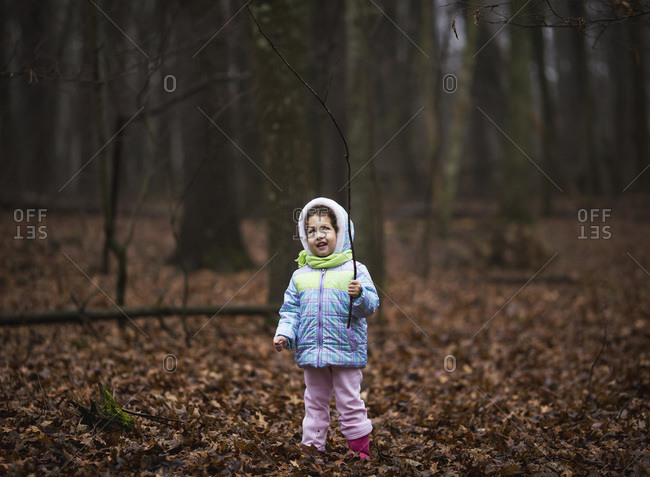 Girl playing with a stick in a forest in winter