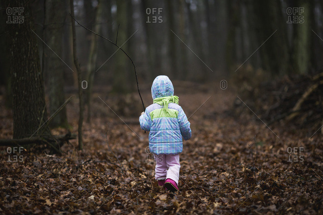 Girl walking in a forest during damp, chilly weather