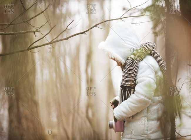 Girl with a toy camera in a forest during winter