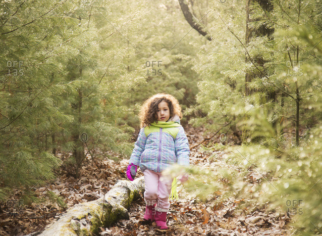 Girl walking through a forest in winter