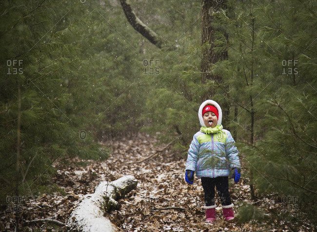 Girl catching snowflakes in the woods