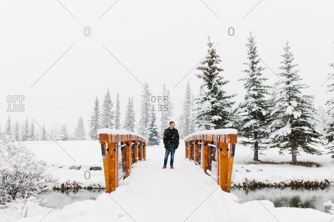 Man standing on a bridge during the snow