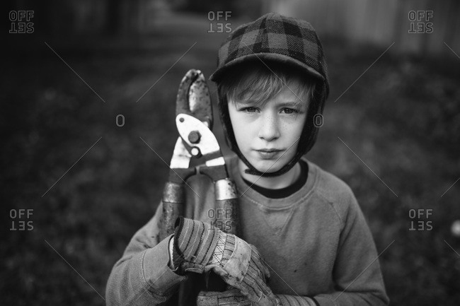 Boy holding tree trimming shears in black and white