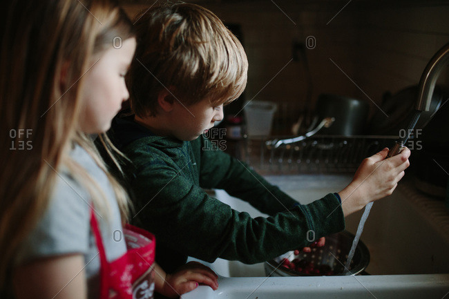 Boy cleaning berries in the sink with his sister watching