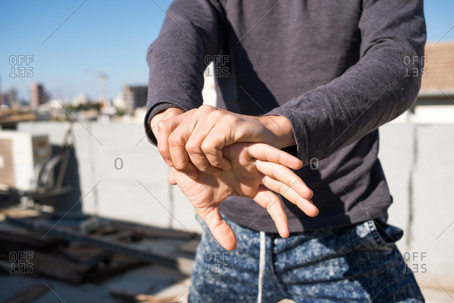 Close-up view of a man's hands while he is stretching his arms