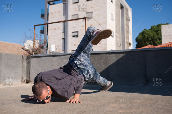 Man breakdancing on the roof of a building